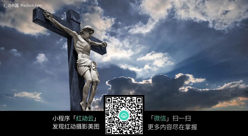 天空下的十字架上的耶稣图片