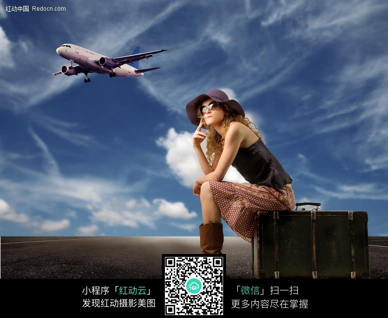 坐在箱子上的外国女人与飞机图片