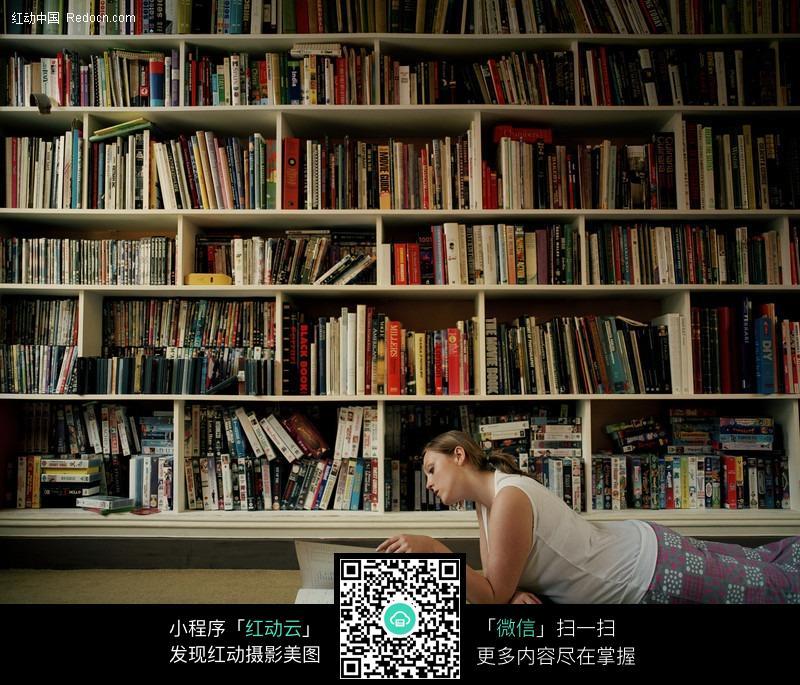书架下趴着看书的外国女人图片