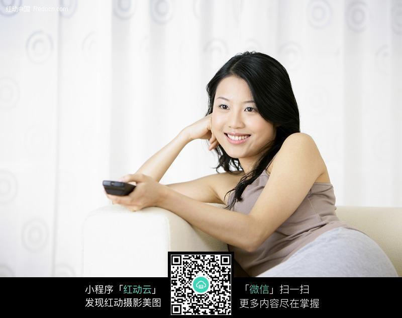 沙发上拿着遥控器的美女图片