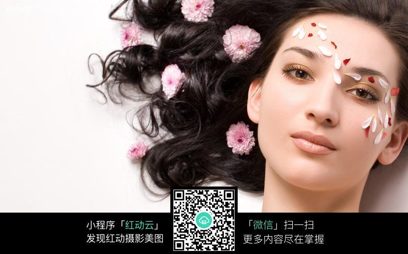 面部撒上花瓣的外国美女图片
