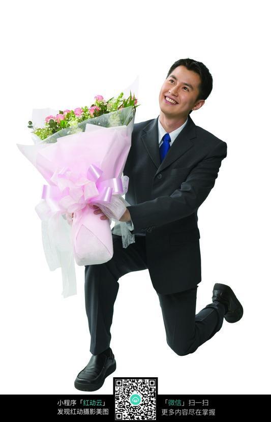 手捧鲜花单膝跪地求婚的男人图片图片