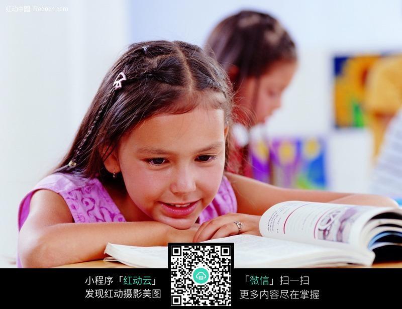 趴在桌子上看书的小女孩图片