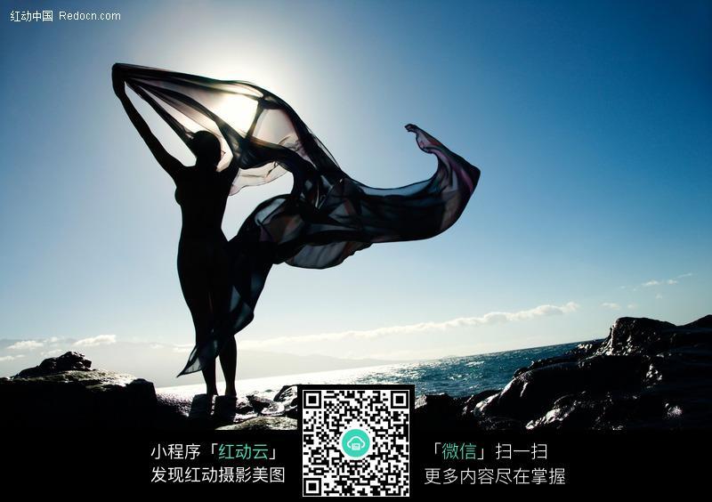 站在海岸边托起飞扬丝绸的美女图片