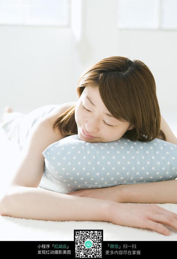 美女趴着抱这枕头睡觉图片