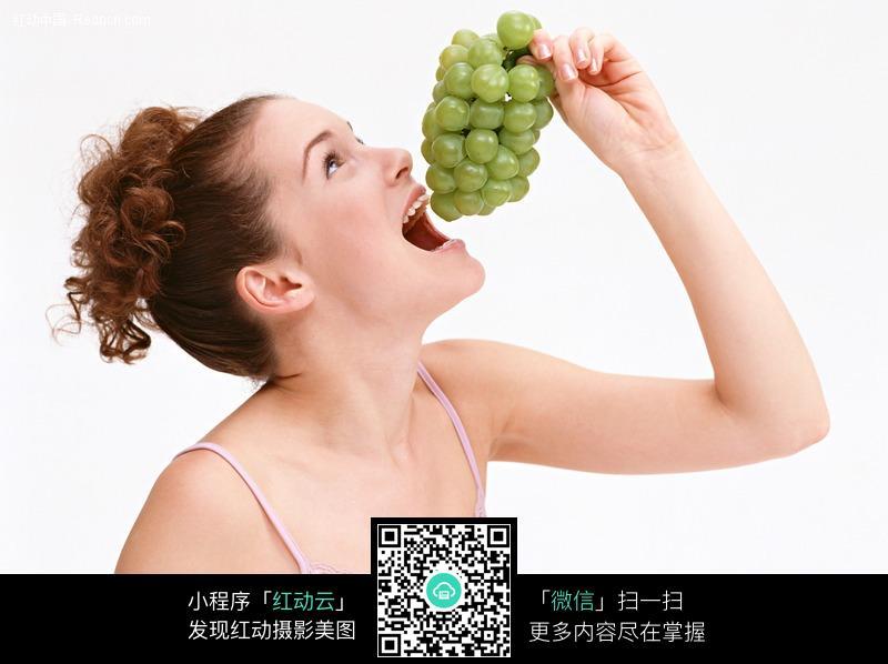张大嘴巴准备吃葡萄的外国美女图片 人物图片