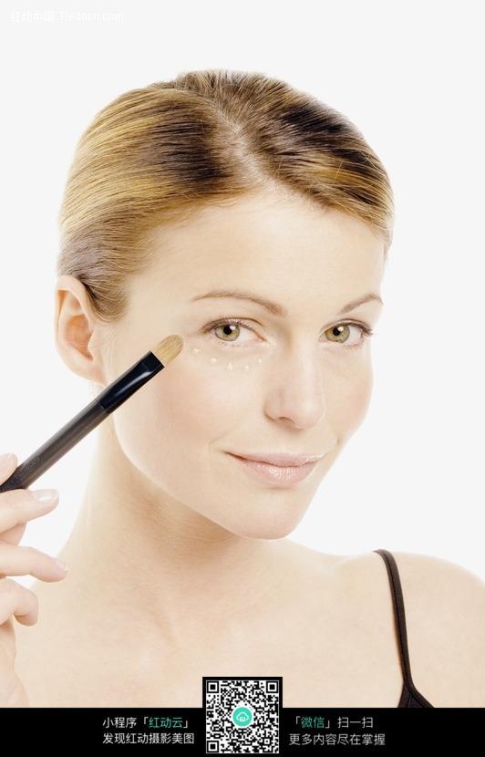 欧洲女士化妆美容 涂遮瑕膏的金发女子图片
