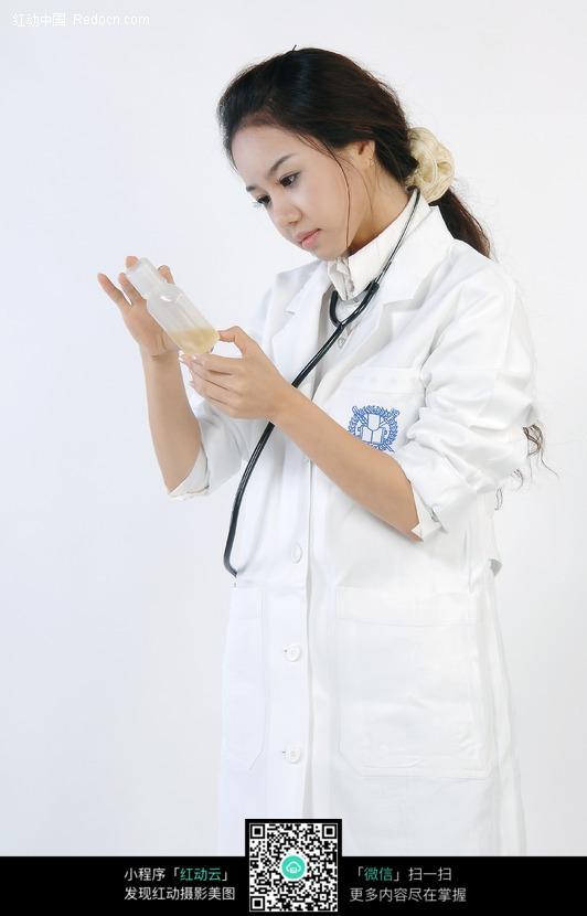 专注看手里药瓶的美女医生图片