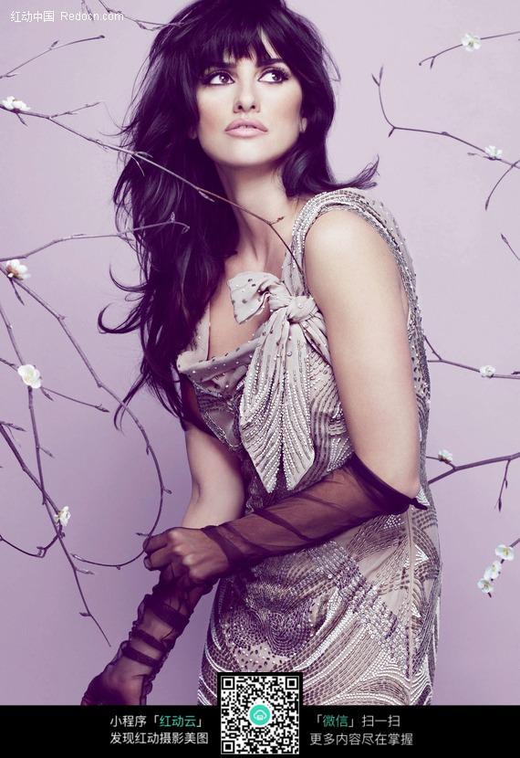 戴黑纱手套站在花枝中的外国美女图片