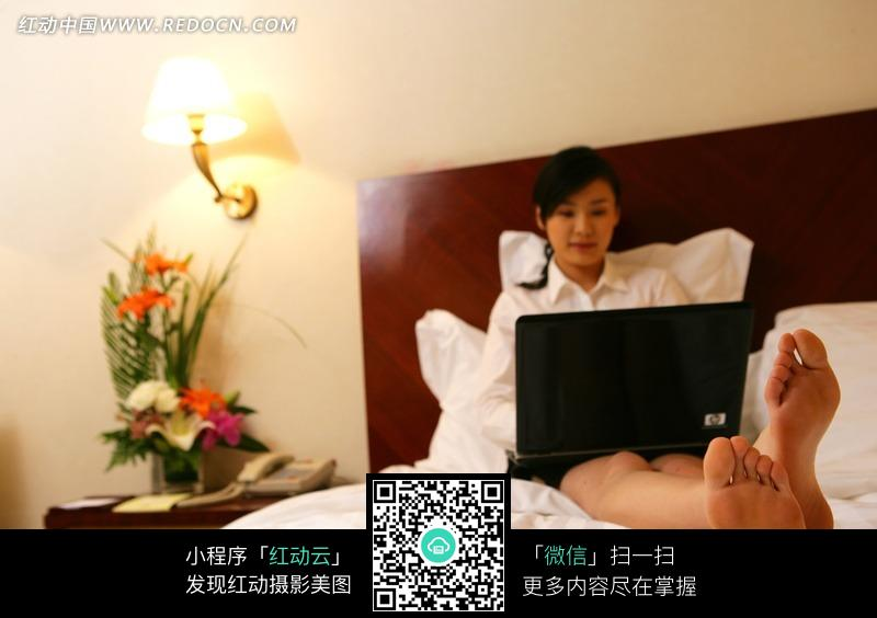 斜靠在床上玩电脑的美女图片
