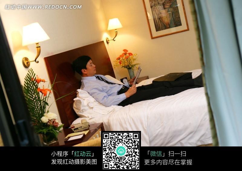 男人趟在床上看书