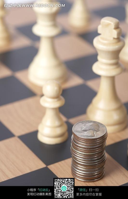 国际象棋棋盘上的棋子和硬币图片图片
