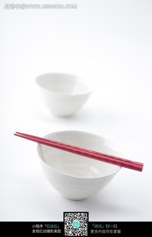 手拿木碗筷子在吃的小男 木制餐桌放着的水杯和碗 桌上的碗筷和杯子