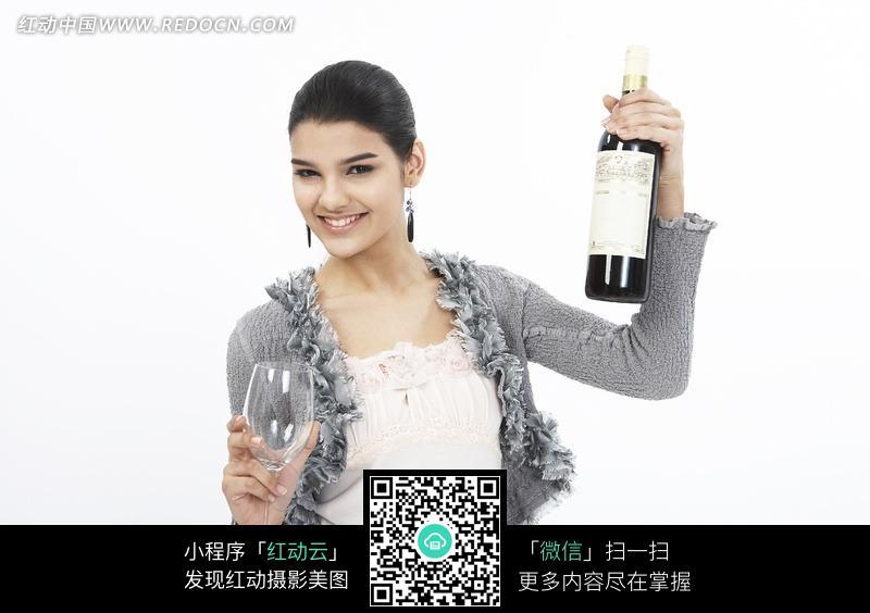 手拿酒瓶和酒杯的时尚女性图片