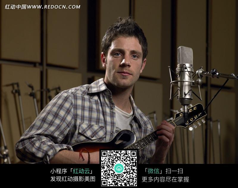 麦克风前弹吉他的外国人