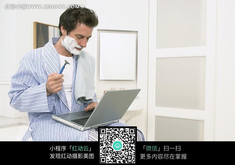 穿着睡衣坐在电脑前边办公边刮胡子的男人图片