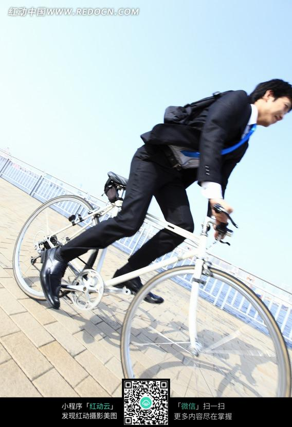 在人行道上骑自行车的男职员图片