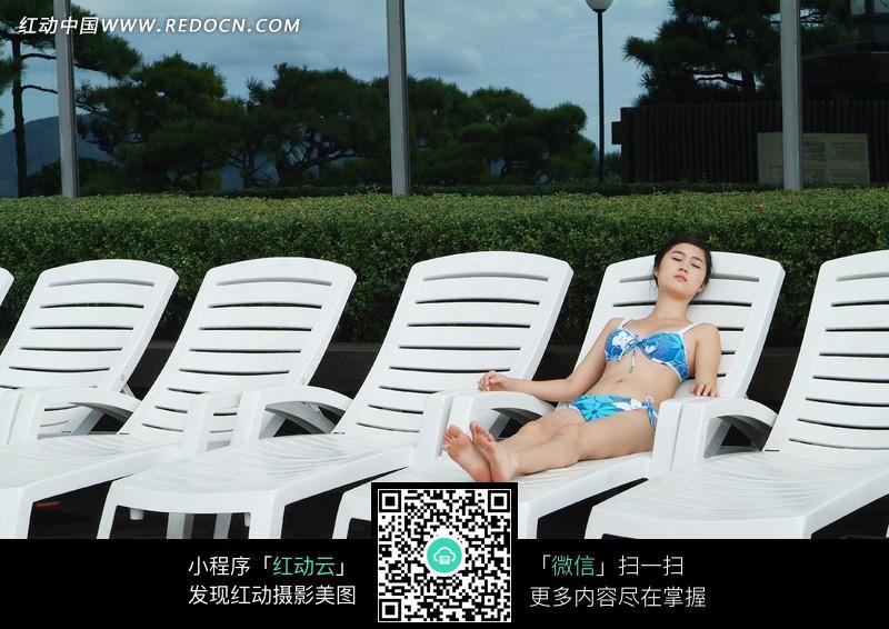 躺在海边白色躺椅上的美女图片图片