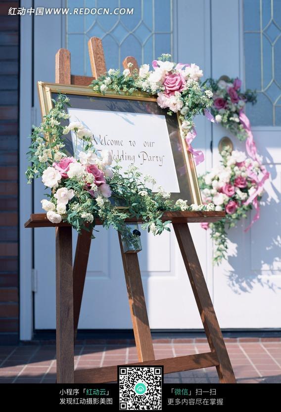 木质画架上放着鲜花装饰的欢迎语
