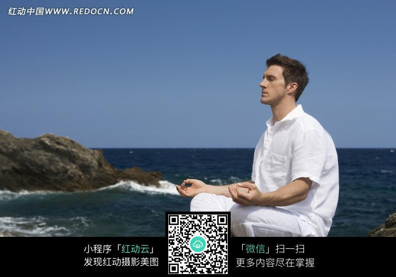 盘腿坐于海边的男子图片
