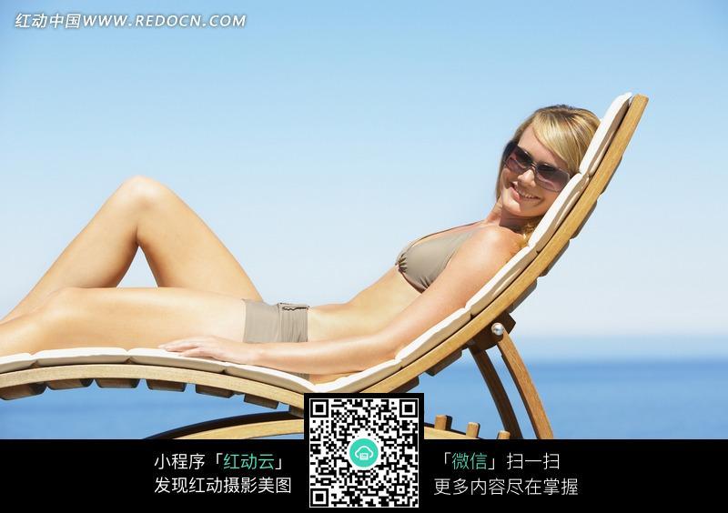 躺在海滩椅子上的女模特照片图片