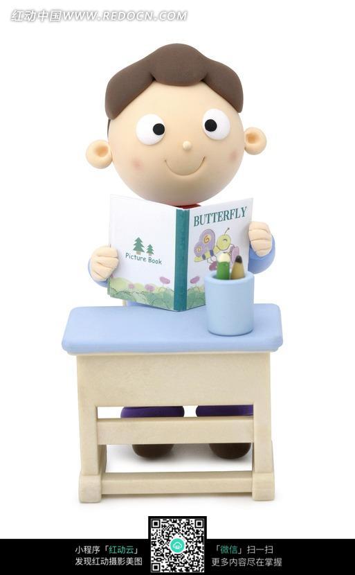 坐在课桌前翻开书本看书的男孩