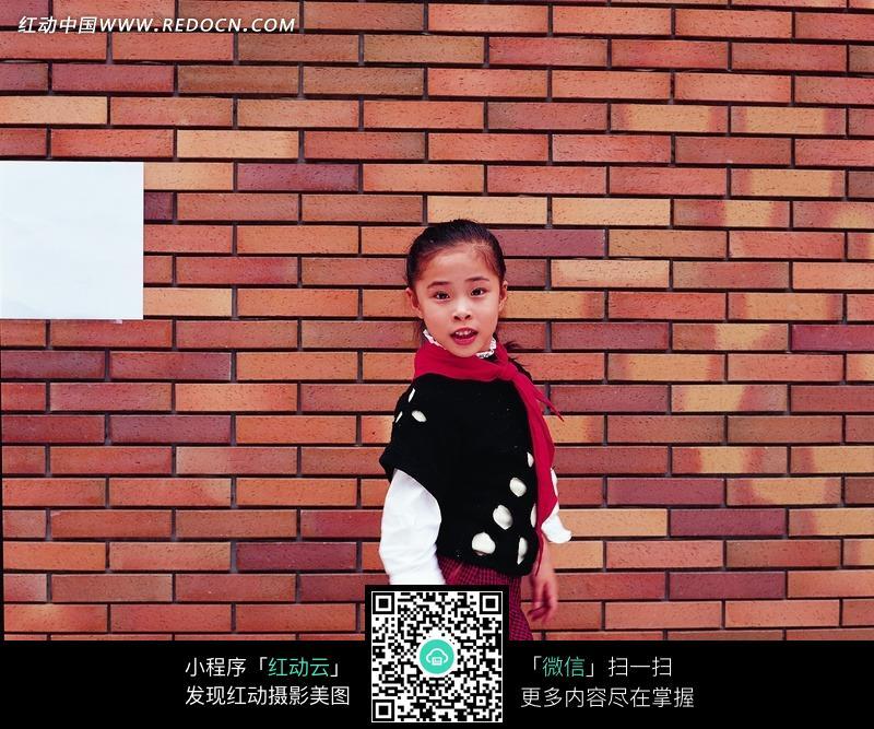 站在红砖墙下面的小女孩图片