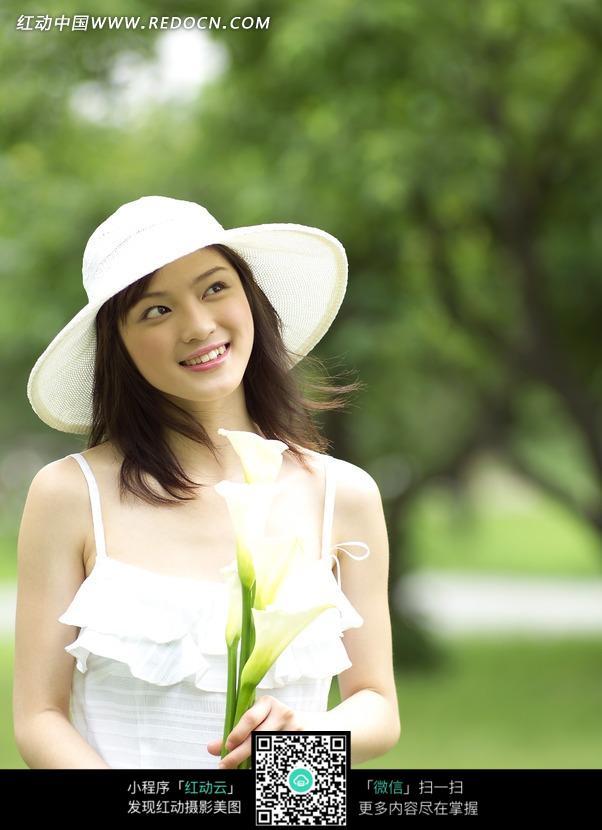 手拿花朵微笑的清纯女孩照片图片