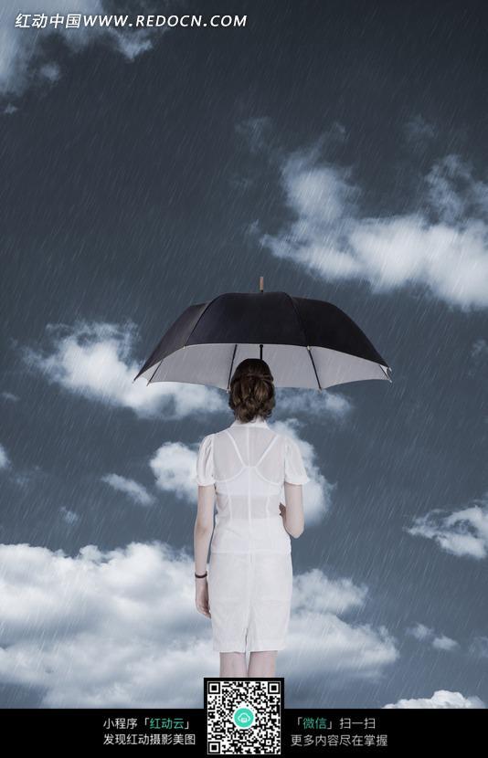 阴天下的女人打着伞的背影