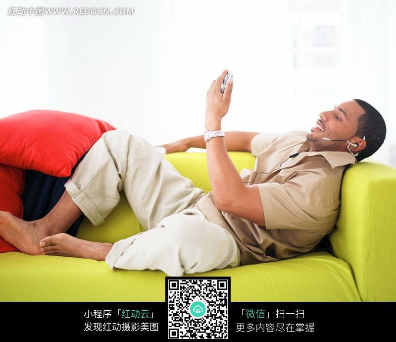 男人黄色网站_躺在黄色沙发上看手机的外国男人