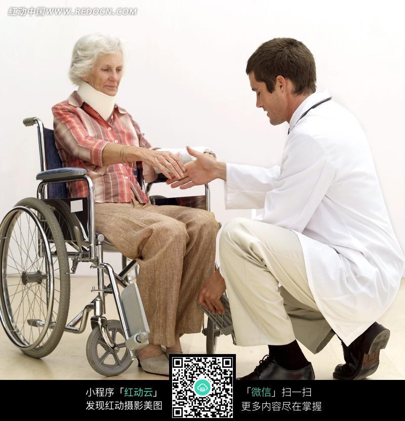 坐在轮椅上的老人和医生握手图片