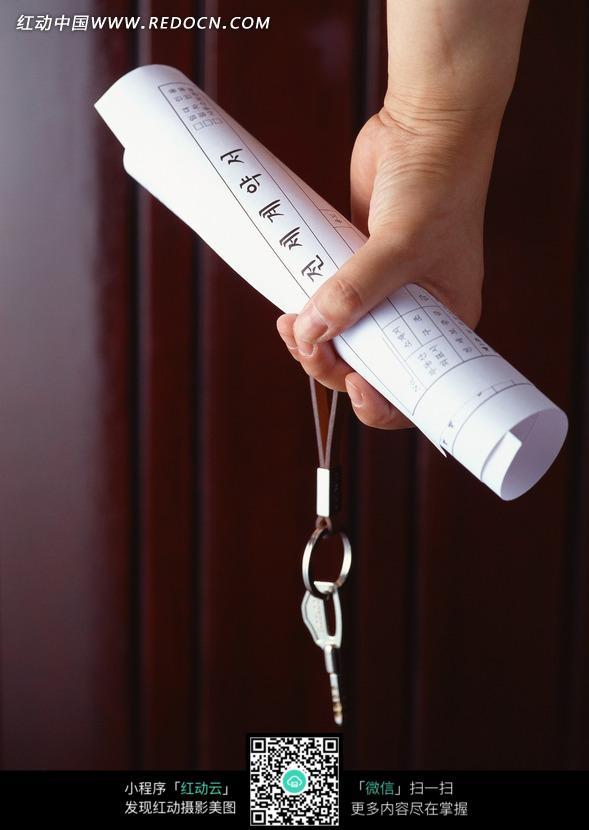 拿着一卷纸和钥匙的手图片