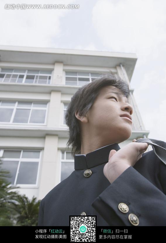 教学楼前背书包侧身回头的日本男中学生
