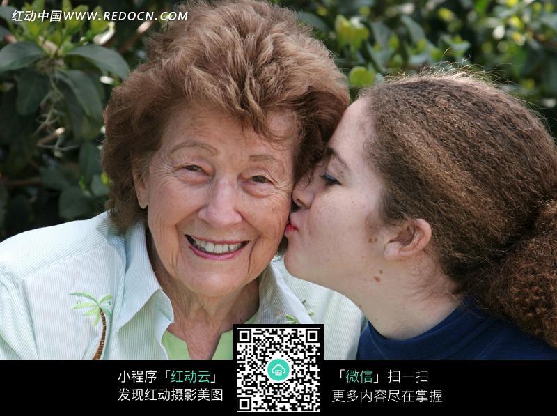 亲吻老奶奶的外国女孩 微笑的外国老奶奶 树林 jpg图片素材 老人 老人