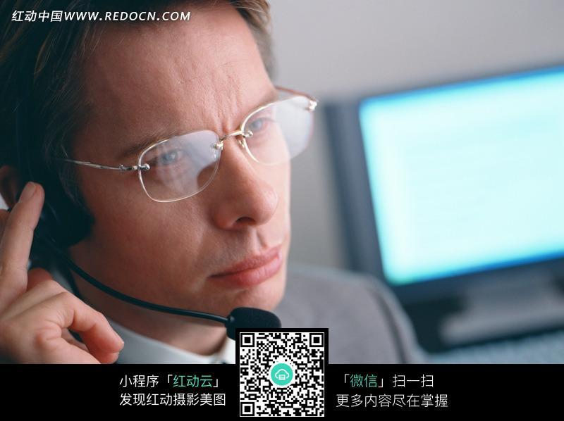 手扶麦克风的戴眼镜的男子图片