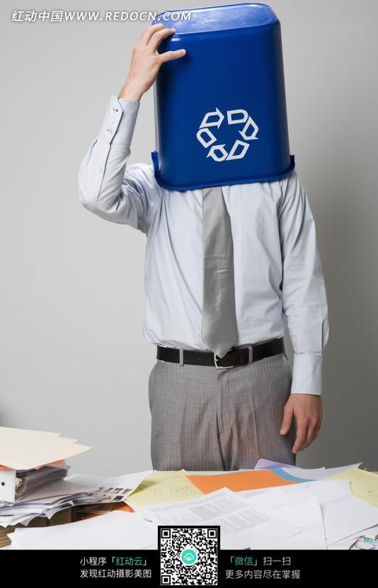 把垃圾桶扣在头上的商务人士图片