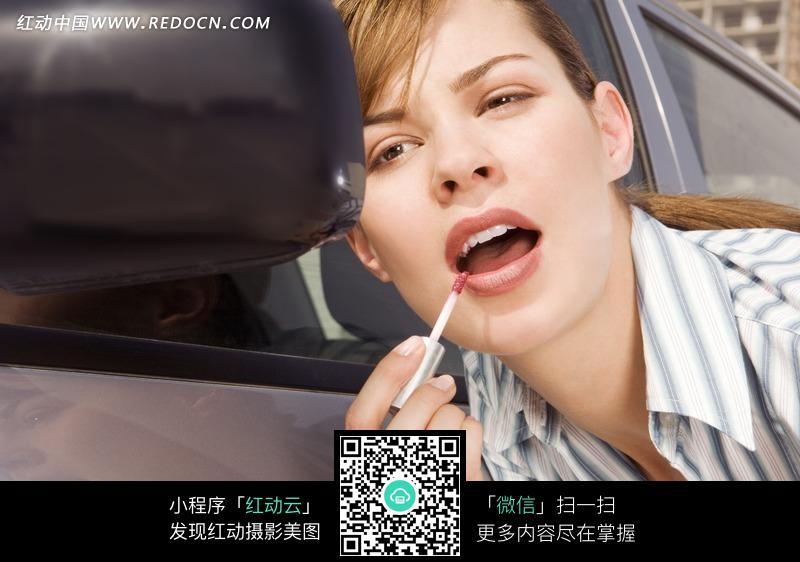 对着车前镜涂口红的女子图片