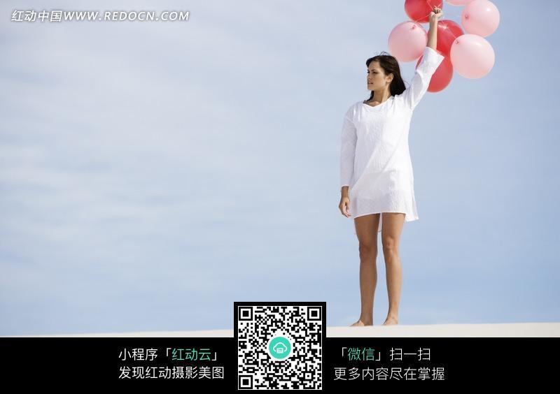 穿白衣服手举红气球的长发美女图片