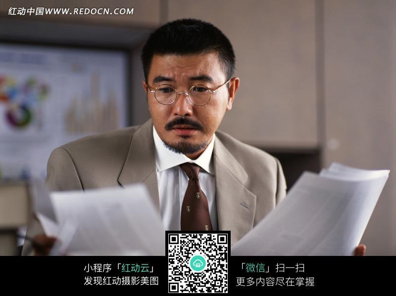 男人开包代表什么_戴眼镜两手比对文件的西装商务男士