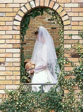拱形门里穿白色婚纱的新娘