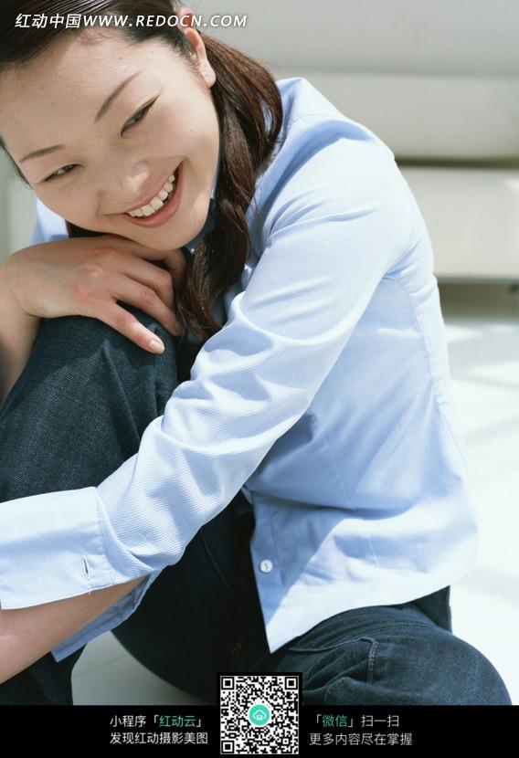 坐着的手抱着膝盖的面带笑容的女子图片_日常