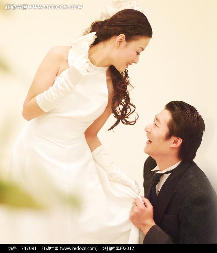 穿婚纱的低头的女子和跪着的男子图片