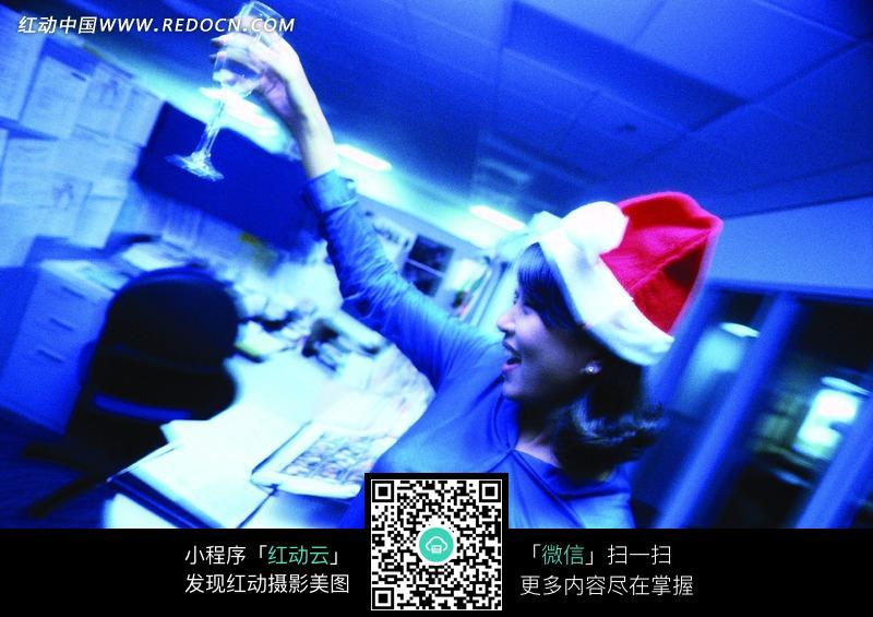 办公室里带着圣诞帽举着酒杯的美女图片图片