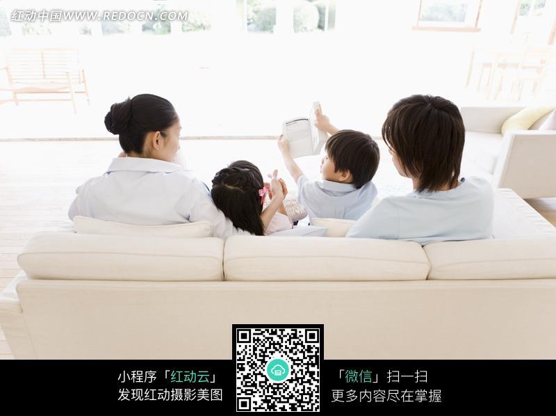 坐在沙发上的一家人的背面照片