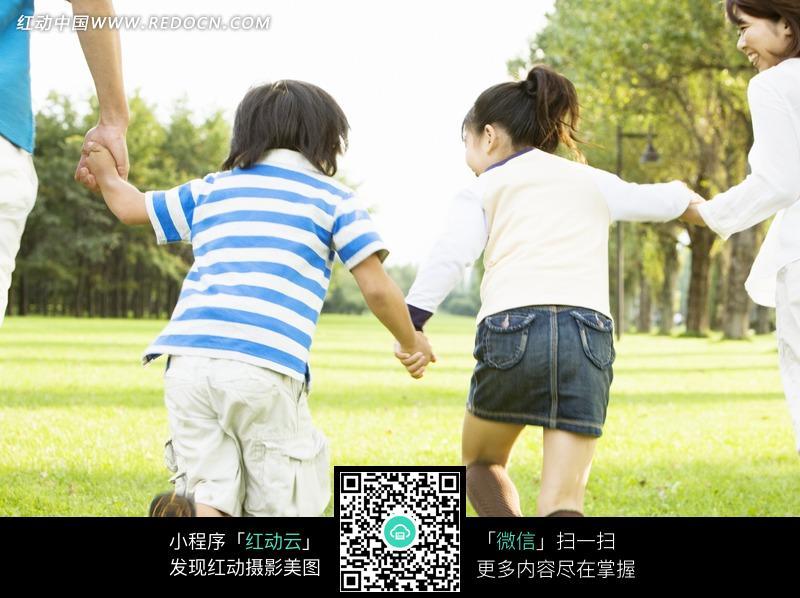 林间绿地手拉手奔跑孩子的背影图片