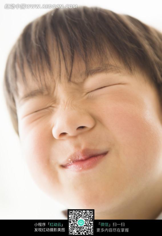 用力闭眼的小男孩脸部特写图片