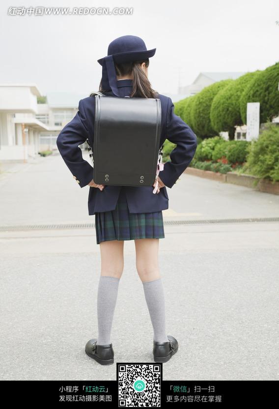 背着黑色书包的穿校服的女孩的背影