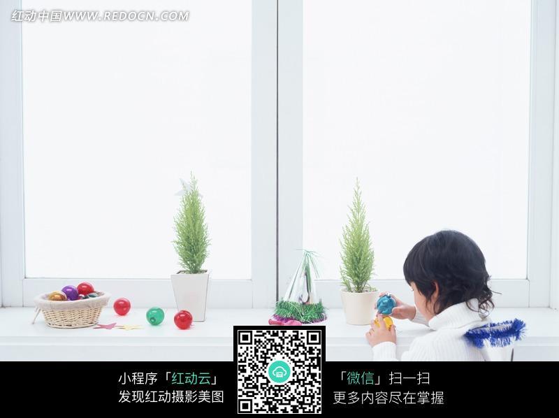 坐在窗台边男孩的背影和盆栽/水晶球/圣诞帽图片图片