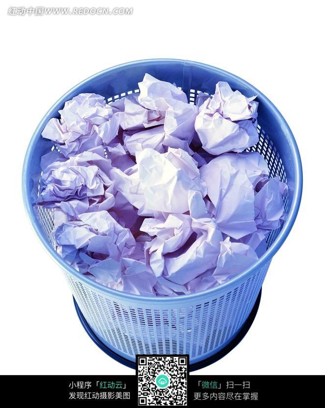 蓝色的垃圾桶和废纸团