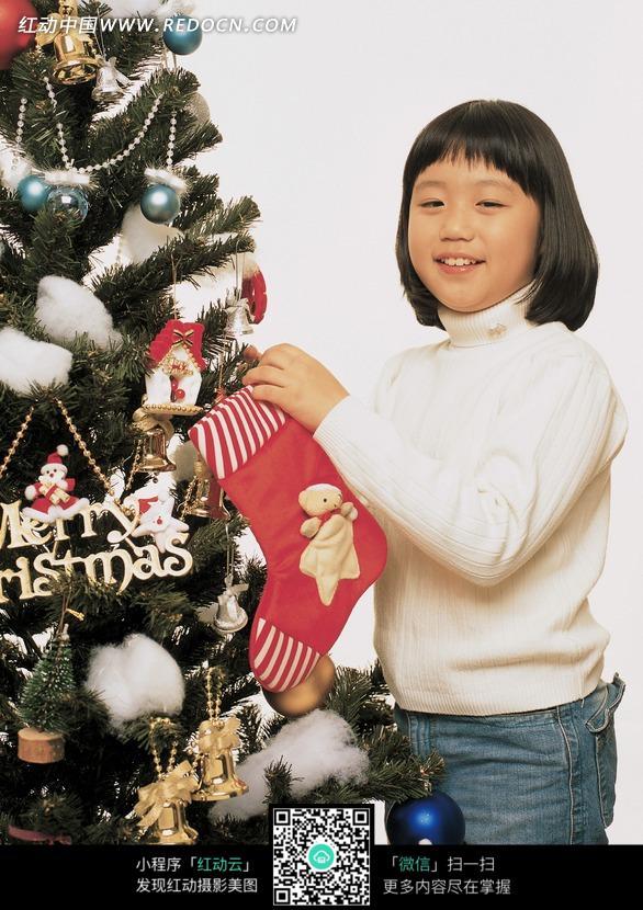 为圣诞树绑圣诞袜的女孩图片